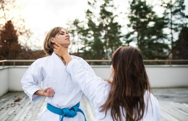 Twee jonge vrouwen beoefenen karate buiten op terras.