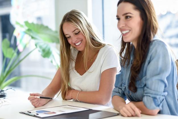 Twee jonge vrouwen bestuderen grafieken op een wit bureau