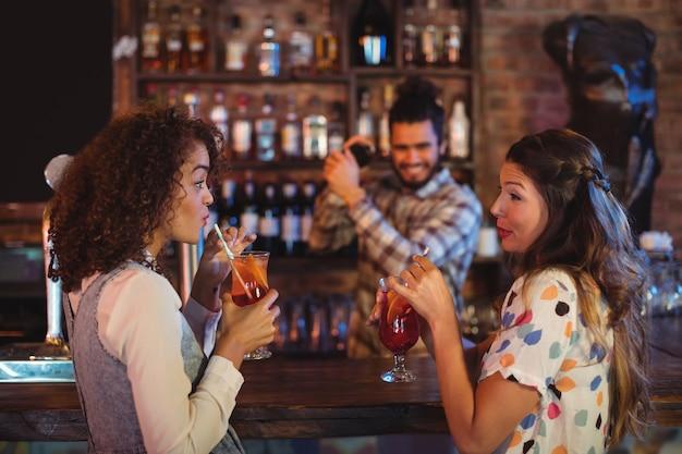 Twee jonge vrouwen die cocktaildranken hebben bij balie