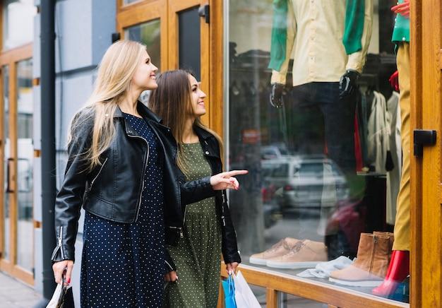 Twee jonge vrouwen die de kleren in het winkelvenster bekijken
