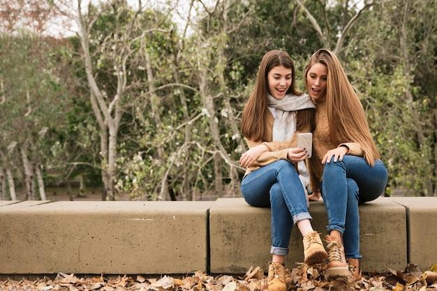 Twee jonge vrouwen die de telefoon in het park bekijken