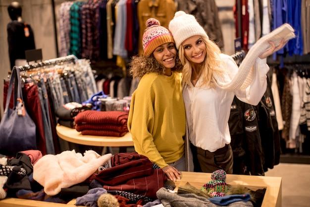 Twee jonge vrouwen die de winterkleren kiezen
