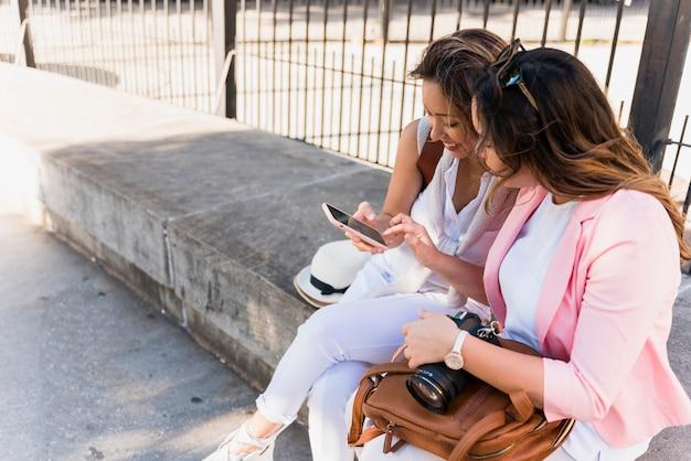 Twee jonge vrouwen die dichtbij het traliewerk zitten die mobiele telefoon bekijken