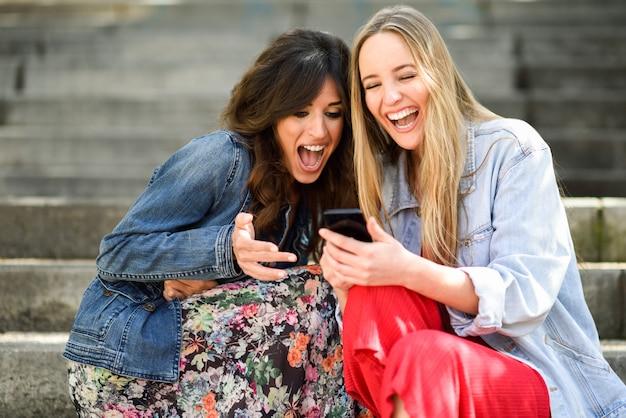 Twee jonge vrouwen die één of ander grappig ding op hun slimme telefoon in openlucht bekijken