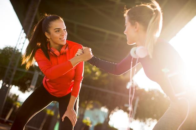 Twee jonge vrouwen die gymnastiek- oefeningen doen openlucht in stedelijk milieu