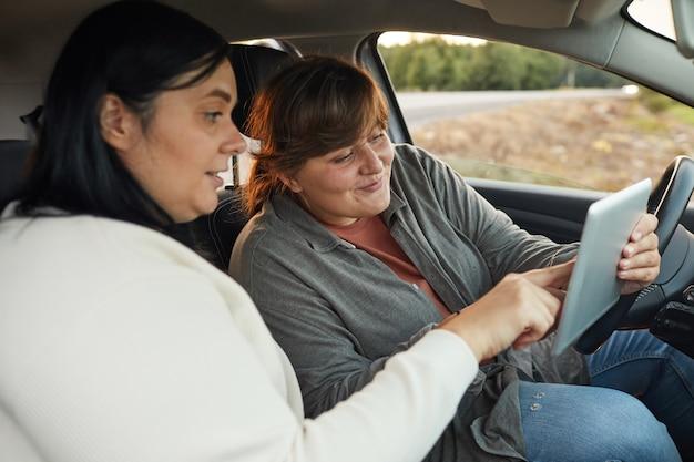 Twee jonge vrouwen die in de auto zitten en navigator op digitale tablet gebruiken tijdens hun reizen