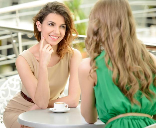 Twee jonge vrouwen die koffie drinken bij het restaurant.