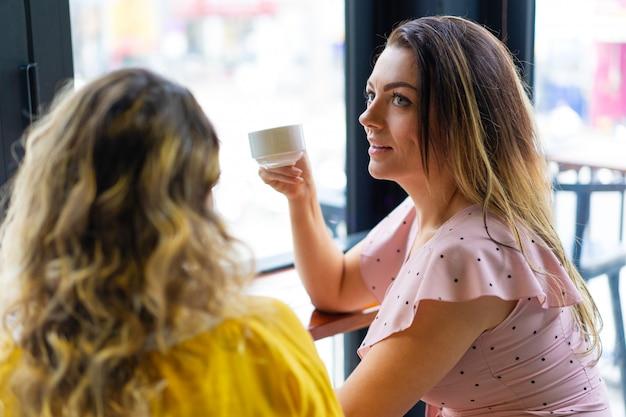 Twee jonge vrouwen die koffie in koffie drinken