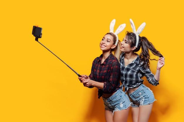 Twee jonge vrouwen die leuke pasen-konijnoren dragen en selfie gebruikend stok maken