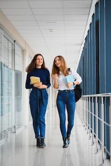 Twee jonge vrouwen die met boek chatten terwijl ze in universiteitsgang staan
