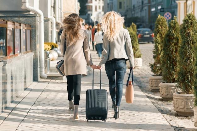 Twee jonge vrouwen die met koffer langs de straat lopen