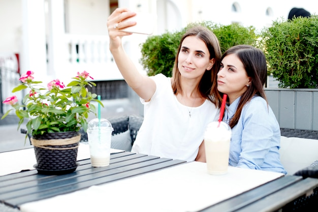 Twee jonge vrouwen die ochtendkoffie drinken en selfie maken