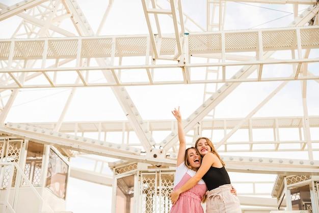 Twee jonge vrouwen die onder het reuzenrad genieten van