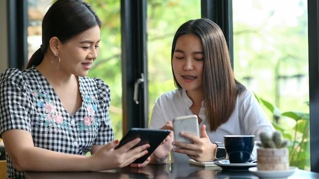 Twee jonge vrouwen die online een smartphone bekijken.