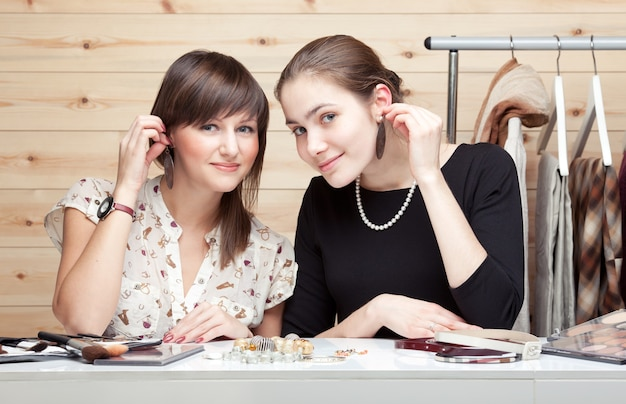Twee jonge vrouwen die oorbellen proberen, accessoires kiezen
