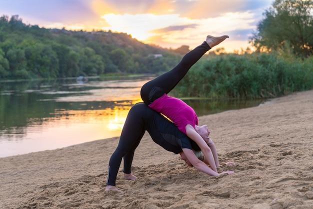 Twee jonge vrouwen die op een zonsondergangstrand uitwerken