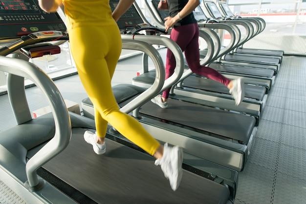 Twee jonge vrouwen die op tredmolen in gymnastiek lopen