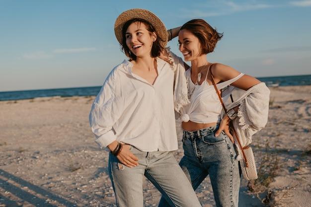 Twee jonge vrouwen die plezier hebben op het zonsondergangstrand, homo lesbische liefde romantiek