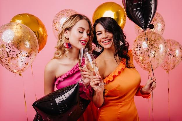 Twee jonge vrouwen die pret hebben op feestje