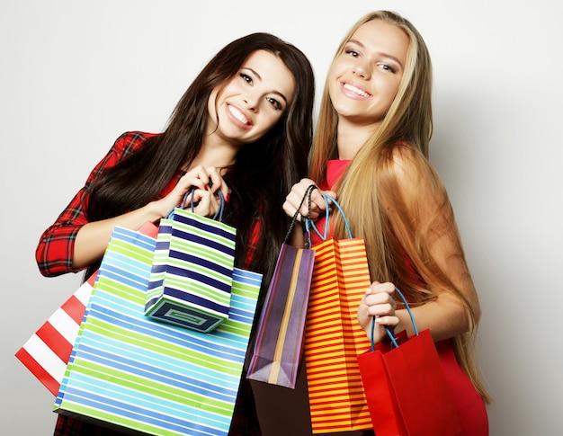 Twee jonge vrouwen die rode kleding met boodschappentassen dragen