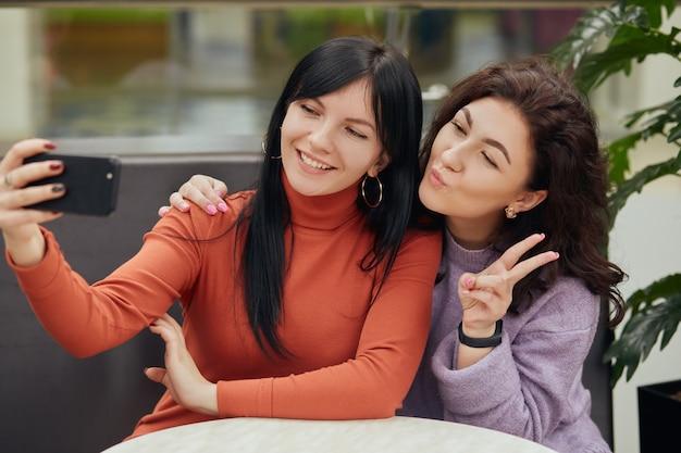 Twee jonge vrouwen die selfie in koffie nemen terwijl het zitten bij lijst, glimlachend en v-teken tonen, vrienden die tijd samen doorbrengen.