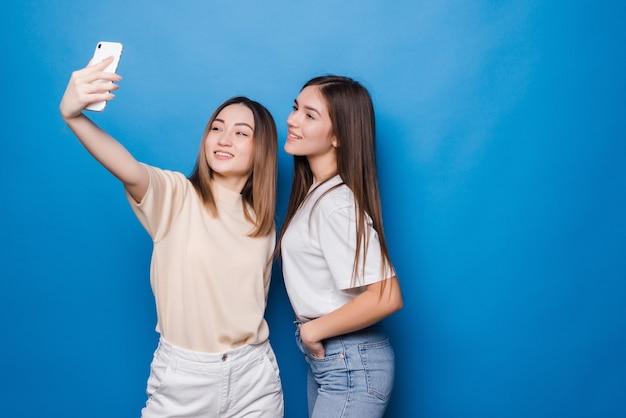 Twee jonge vrouwen die selfiefoto over blauwe muur maken