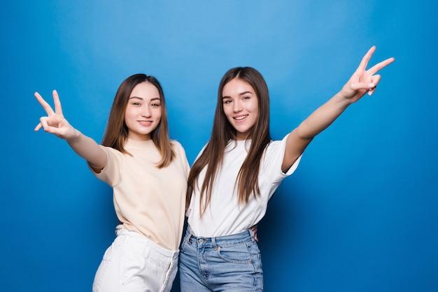 Twee jonge vrouwen die vingers tonen die overwinningsteken doen dat over blauwe muur wordt geïsoleerd. nummer twee.