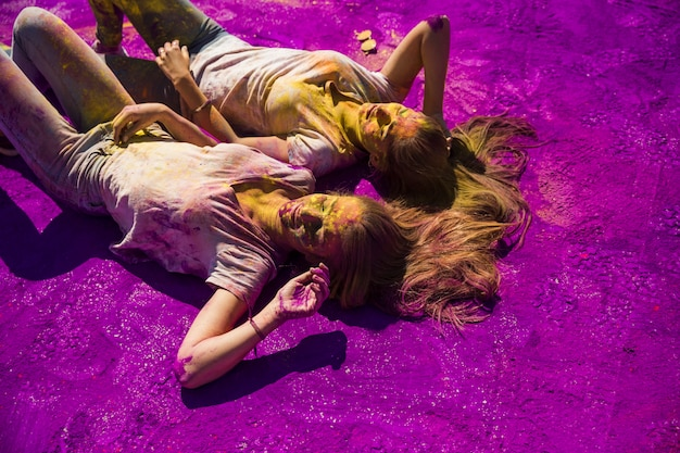 Twee jonge vrouwen die zij aan zij op purper holipoeder liggen