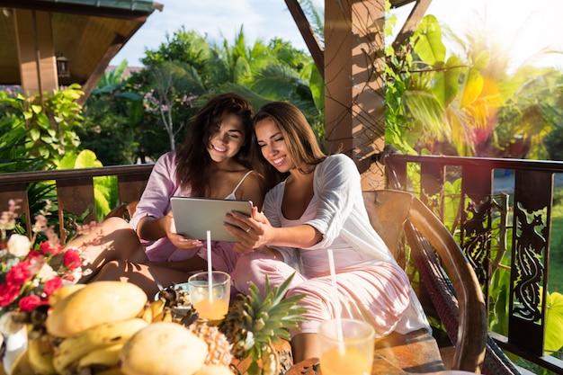 Twee jonge vrouwen gebruiken digitale tablet tijdens het ontbijt op het terras