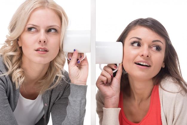 Twee jonge vrouwen gebruiken een mok om naar elkaar te luisteren.