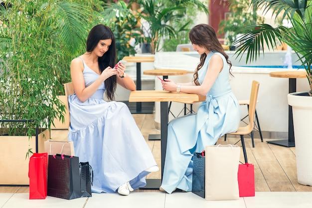 Twee jonge vrouwen gebruikt slimme telefoon na openlucht winkelen bij koffie