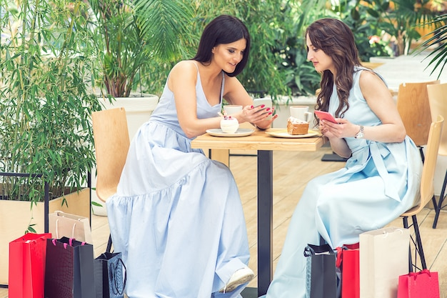 Twee jonge vrouwen gebruikt smartphone na in openlucht winkelend bij koffie.