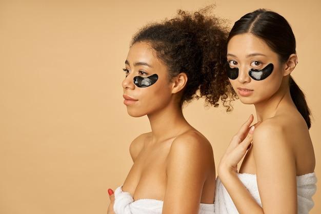 Twee jonge vrouwen gewikkeld in een handdoek poseren met aangebrachte zwarte hydrogel onder ooglapjes