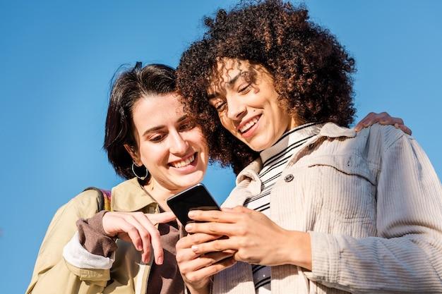 Twee jonge vrouwen glimlachen terwijl ze naar de telefoon kijken