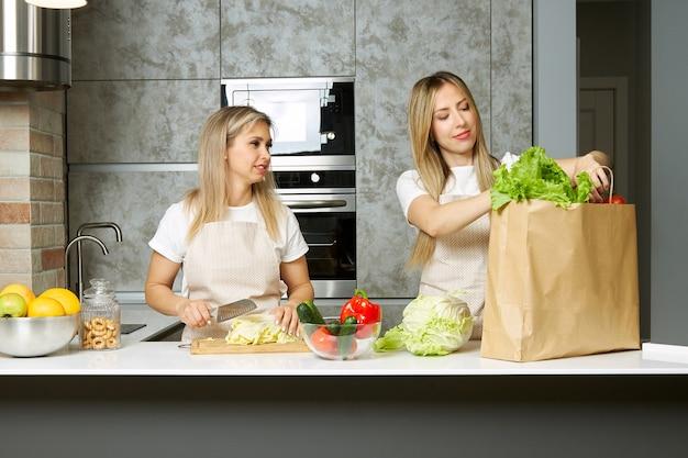 Twee jonge vrouwen halen een papieren zak met boodschappen uit elkaar en koken