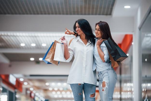 Twee jonge vrouwen hebben samen een dagje winkelen in de supermarkt.