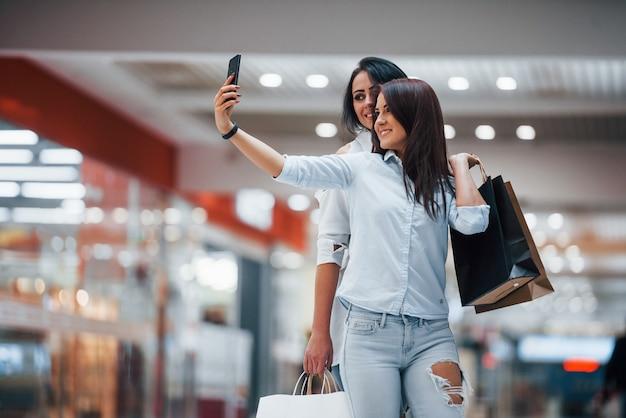 Twee jonge vrouwen hebben samen een winkeldag in de supermarkt en maken selfie.