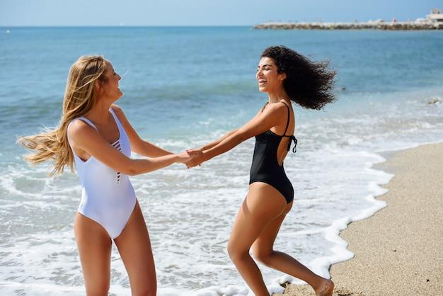 Twee jonge vrouwen in badkleding die pret met hun die handen hebben op het strand worden gevangen.