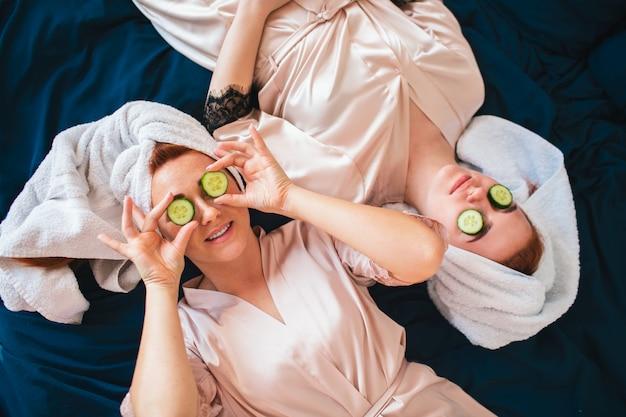Twee jonge vrouwen in handdoeken en pyjama's hebben samen een leuk spa-feest in huis.
