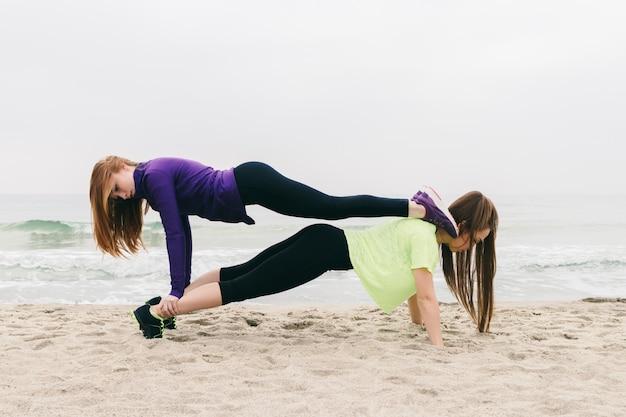 Twee jonge vrouwen in sporten kleden het doen van een gymnastiek- oefening op het strand
