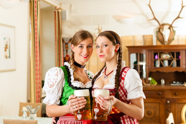 Twee jonge vrouwen in traditionele beierse klederdracht in restaurant of pub