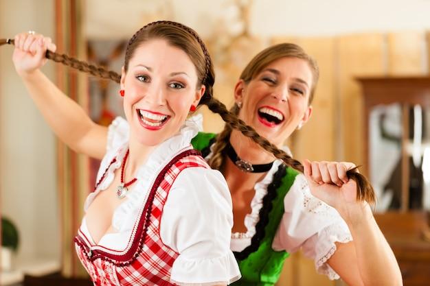 Twee jonge vrouwen in traditionele beierse klederdracht in restaurant of pub
