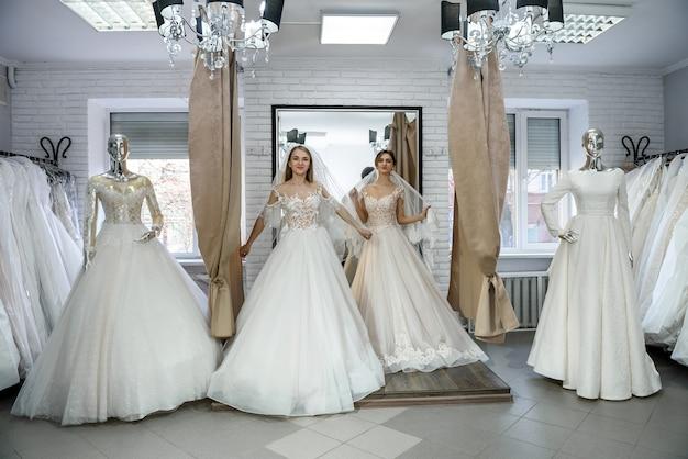 Twee jonge vrouwen in trouwjurken poseren voor spiegel