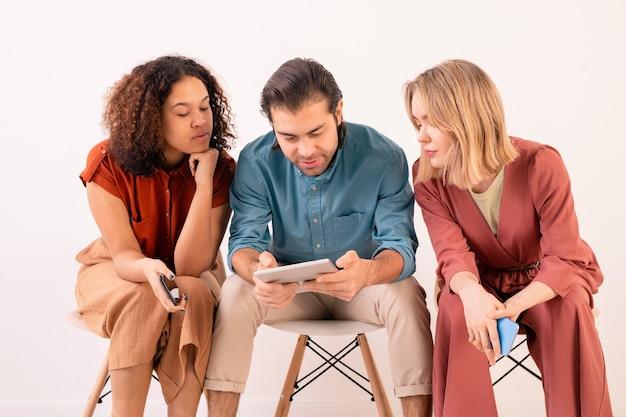 Twee jonge vrouwen in vrijetijdskleding kijken naar scherm van touchpad vastgehouden door man tijdens het kijken naar online film of sociale netwerken video