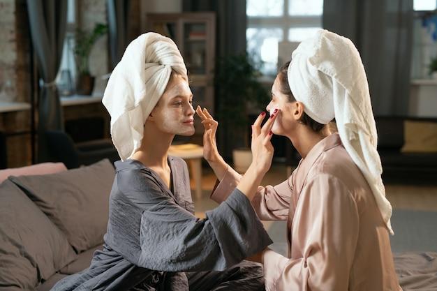Twee jonge vrouwen in zijden pyjama's en handdoeken op hoofden die kleimaskers op elkaars gezichten aanbrengen terwijl ze thuis genieten van een spabehandeling