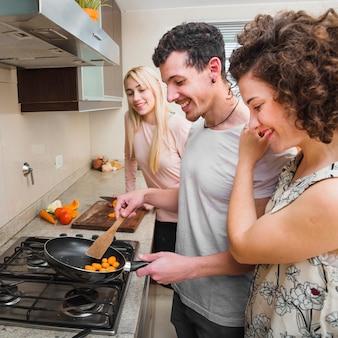 Twee jonge vrouwen kijken naar man braden plakjes wortel in de koekenpan