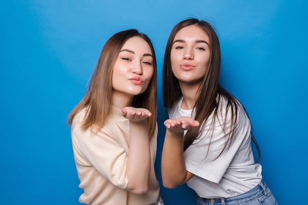 Twee jonge vrouwen klappen kus geïsoleerde blauwe muur