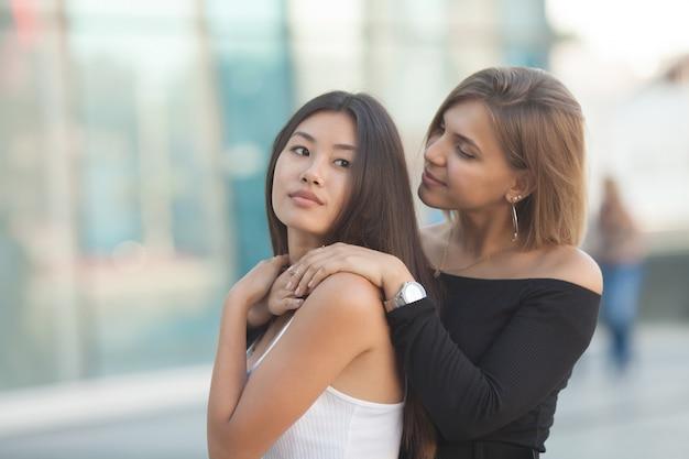 Twee jonge vrouwen knuffelen buitenshuis. aziatisch meisje dat de camera en het glimlachen bekijkt. beste vrienden