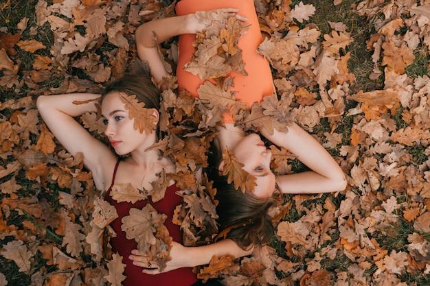 Twee jonge vrouwen liggend op de grond en bedekt met herfstbladeren en kijken naar verschillende richtingen.