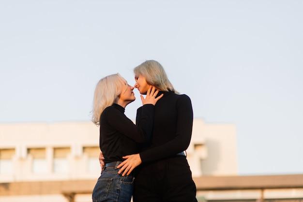 Twee jonge vrouwen lopen glimlachend omhelst en kussen buiten in de stad